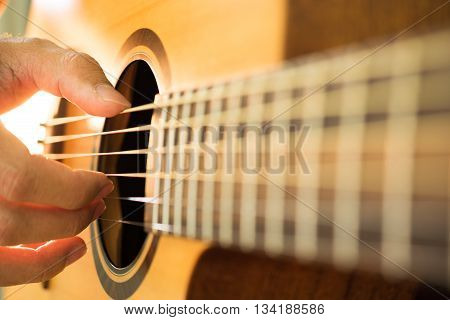 Close up of guitarist hand playing acoustic guitar.