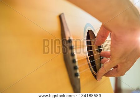 Close up of Man's hands playing acoustic guitar.