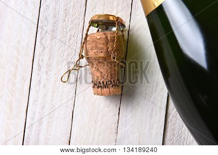 Top view of a bottle of champagne next to a cork on a rustic white wood table. Horizontal format with copy space.