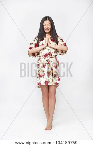 Picture of fashion asian lady in summer or spring dress in studio clasped her hands in front of her. Happy woman smiling for camera.