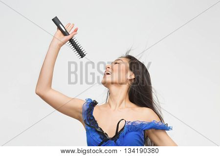 Fashion asian model in blue lingerie singing songs in studio. Attractive brunette holding microphone in front of her over white background.