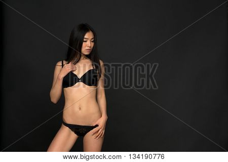 Picture of brunette fashion asian model in black lingerie or underwear in studio. Attractive and gorgeous woman looking down over grey background.