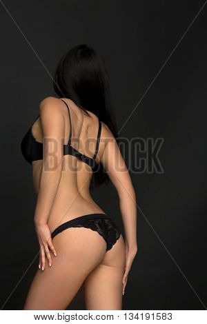 Picture of beautiful lady touching her body isolated on dark grey background. Attractive fashion asian model showing her back while posing in black lingerie or underwear in studio.