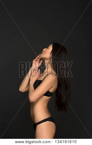 Profile of brunette woman looking upwards over grey background. Attractive fashion asian model in black lingerie or underwear in studio.