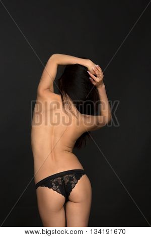 Fashion asian model in black lingerie in studio. Topless woman showing her gorgeous back over black background.