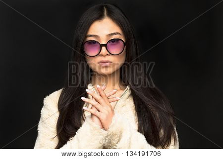 Portrait of fashion asian model woman in sunglasses clasped her hands in front of her and looking at camera in studio.