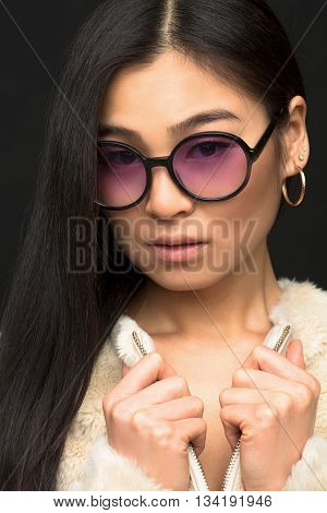 Closeup portrait of attractive fashion asian model woman posing in sunglasses in studio. Beautiful lady in white coat over black background.