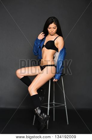 Picture of fashion asian model in black lingerie or underwear sitting on chair in studio. Pretty lady with black hair over grey background.