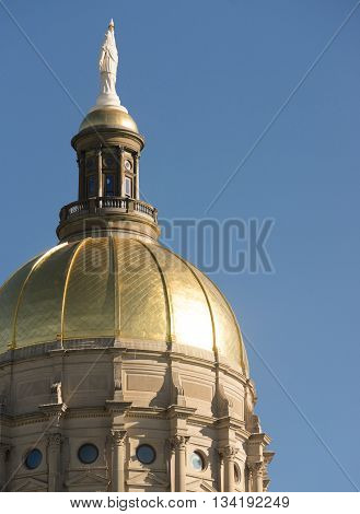 The golden capital dome stands out against a blue sky in Atlanta