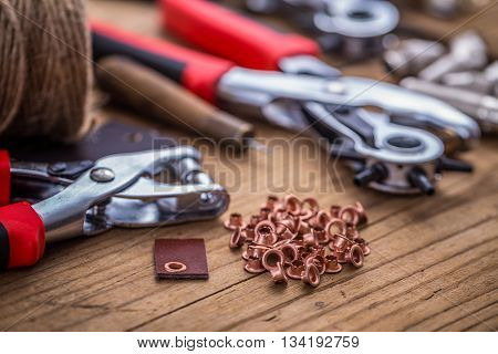 Eyelet and rivet setting punch tools on wooden background