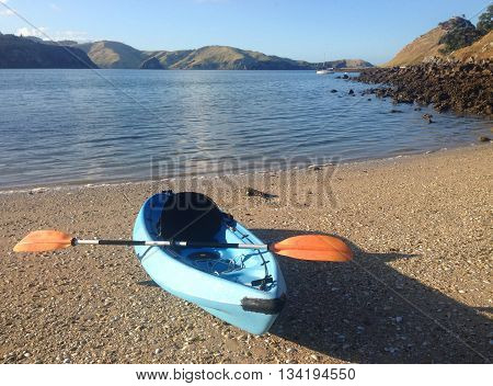 Kayaking at Te Kouma in the Coromandel Peninsula, New Zealand, at a shelly and sandy beach, with green hills and blue sky in the distance.