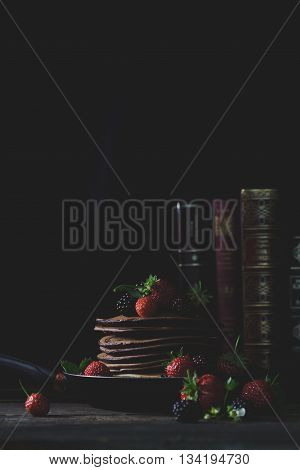 Pancakes in the rusty pan with strawberries and blackberries honey and old books in background with mystical light veritical poster