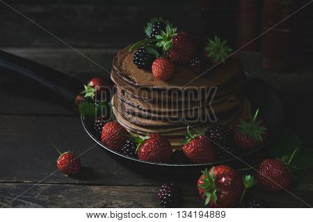 Chocolate pancakes in rusty pan with organic fruits like strawberries and blackberries