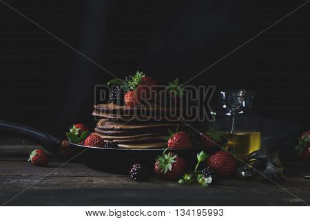 Chocolate pancakes in the rusty pan with strawberries blackberries and honey in dark backgound with mystical light