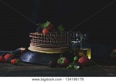 Ombre pancakes in the rusty pan with strawberries blackberries and honey in dark backgound with mystical light