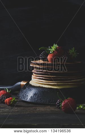 Chocolate pancakes in rusty pan with organic fruits like strawberries and blackberries on old wooden table vertical