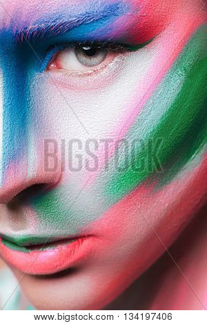 Beautiful fashion woman with bright color face art and body art. Paint on face. Creative portrait