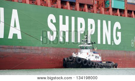 Oakland CA - June 09 2016: AmNav Tugboat LIBERTY off the port side of cargo ship CSCL WINTER assisting the vessel to maneuver into the Port of Oakland.