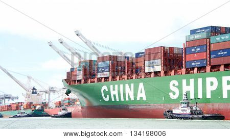 Oakland CA - June 09 2016: Multiple tugboats work together to maneuver cargo ship CSCL WINTER into the Port of Oakland the fifth busiest port in the United States.