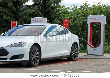 PAIMIO, FINLAND - JUNE 4, 2016: White Tesla Model S electric car is being charged at Tesla Supercharger station. Charging the battery from 10 to 80 percent takes about 40 minutes.