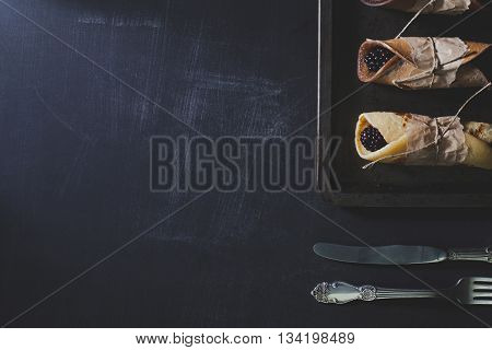 Pancakes with blackberries on rusty tinwere with silver knife and fork on scratched blackboard flat kay