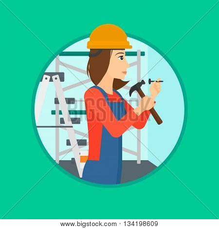 A female worker hammering a nail into the wall. Worker in overalls and hard hat nailing with hammer in apartment. Vector flat design illustration in the circle isolated on background.