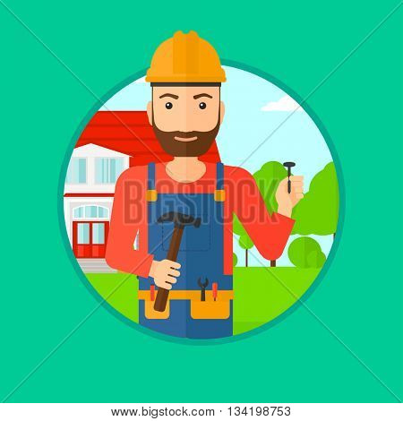A hipster builder with the beard in uniform and helmet. A builder with hummer and nail in hands. Builder on a background of house. Vector flat design illustration in the circle isolated on background.