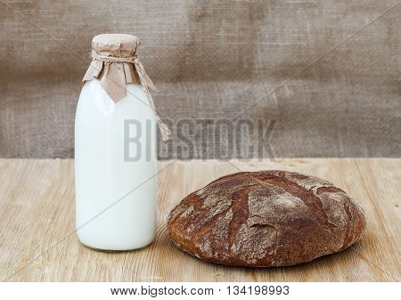 Rye bread with full bottle of milk on wooden table