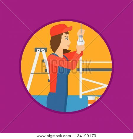 A female electrician twisting a light bulb. An electrician installing light in an apartment. Electrician changing light bulb. Vector flat design illustration in the circle isolated on background.