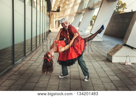 woman in dance has jumped on the old man they in a retro garb.