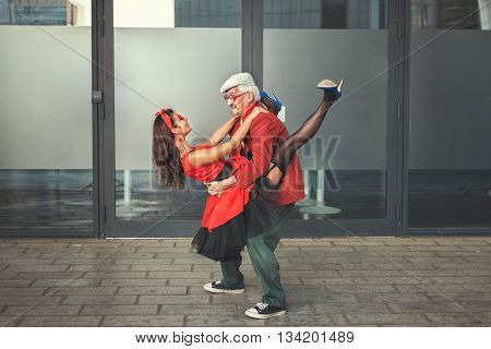 The old man holds the young woman on hands they dance.