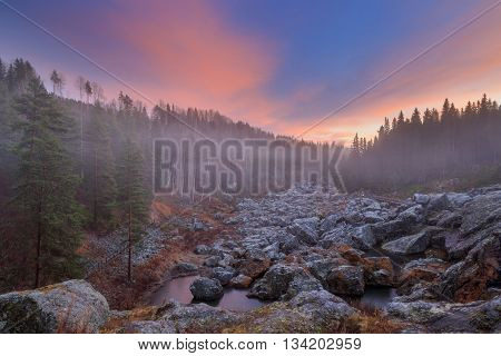 evening forest mountain landscape with mist and ice on water
