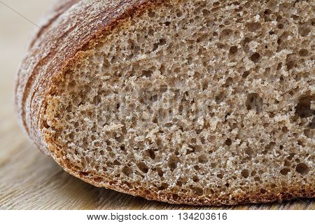 Fresh brown rye bread on a rustic wooden table close up