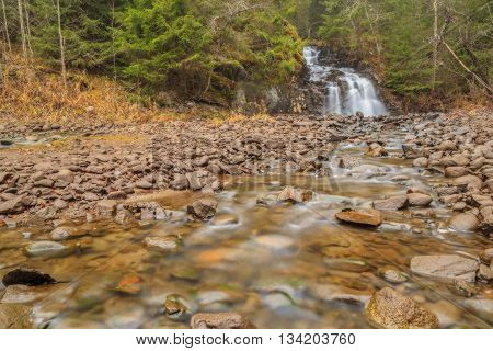 waterfall with rocks and trees in autumn with mist