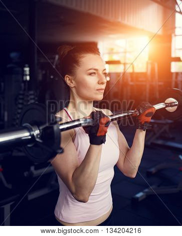 Young beautiful woman doing biceps curl with EZ curl bar in a gym. Athletic girl doing workout in a fitness center with sunset beams in the window poster