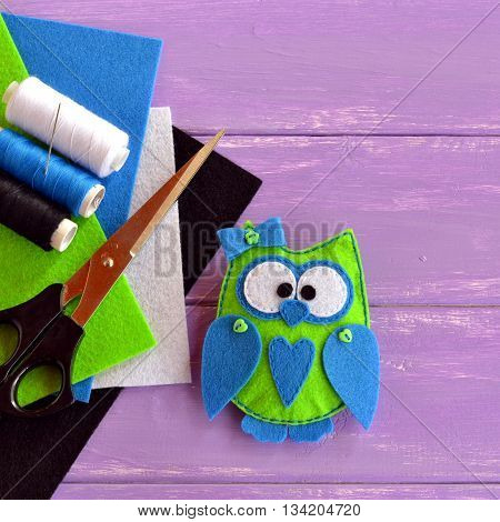 Cute felt owl ornament. Owl is sewn from green and blue felt and decorated with small buttons. Hand fabric embellishment idea. Felt kit, thread, needle, scissors on lilac wooden background