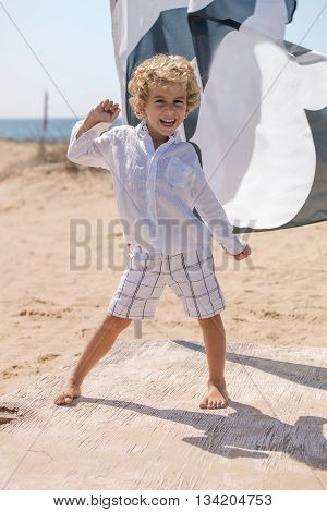 Small Child Kidding Standing On A Beach