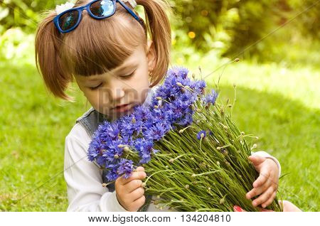 little girl holding a bouquet of blue flowers