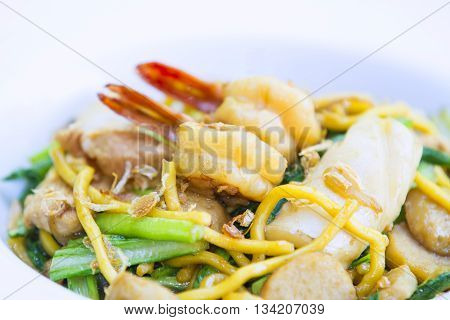 Paad laad na talay Fride noodle on top with seafood and sauce.
