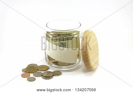 Banknote and coins in glass jar with copy space on the jar