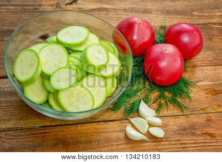 Sliced zucchini, ripe red tomato, garlic cloves and dill on a wooden cutting board on the table