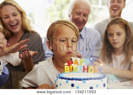 Boy Blows Out Birthday Cake Candles At Family Party