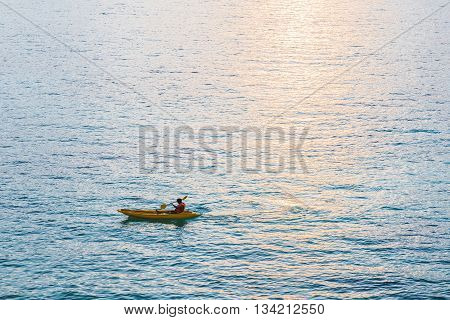 Kayak, a guy kayaking on blue ocean in sunset with sunlight reflection on the sea
