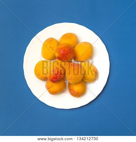 Apricots on a plate. Blue background
