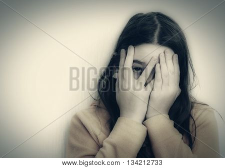 Frightened teen girl looks through fingers. Monochrome photography