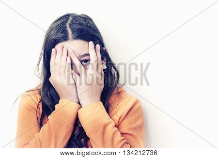 Frightened teen girl looks through fingers.