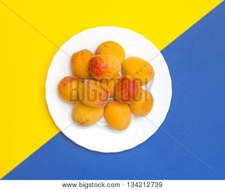 Apricots on a plate. Blue and yellow background