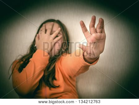 Frightened Teenage Girl Making Stop Gesture. Selective focus on hand