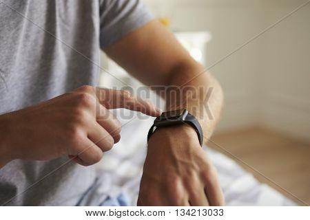 Man Wearing Pajamas Checking Smart Watch In Bedroom