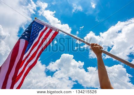American flag with stars and stripes hold with hands against blue sky